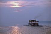 Kreuzfahrtschiff fährt auf der Wolga dem Sonnenuntergang entgegen