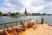 View of river, boats, buildings and temples from deck of boat in Bangkok