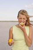 Frau beißt in Zitronenscheibe und verzieht das Gesicht