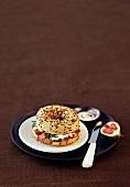 Bagel mit Schinken und Feta und Feige auf einem braunen Teller