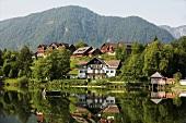 Seelandschaft mit Fischerboot, Häusern und Bergen