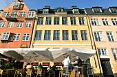 Bunte Häuser im Nyhavn in Kopenhagen , am Bürgersteig ein Café.