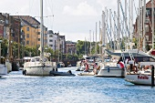 View of canal with boats moored at harbour in Christianshavn, Copenhagen, Denmark
