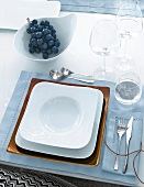 Gedeck in Weiß und Blau, Teller quadratisch, Platzteller kupferfarb.