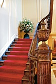 Staircase with red carpet and wooden railings at Hotel Dixseptieme in Brussels, Belgium