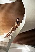 Seductive woman wearing brown bikini sitting on white stone staircase