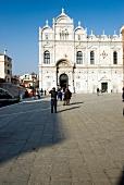 Tourist and Scuola Grande di San Marco at Campo San Giovanni e Paolo square, Venice, Italy