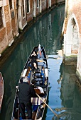 Tourists enjoying gondola ride in narrow canal, Venice, Italy, elevated view