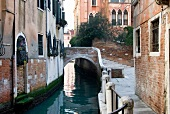 View of narrow canal, railing, houses and bridge in Campiello Barbaro, Venice, Italy