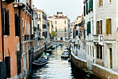 View of buildings, foot bridge and narrow canal in Venice, Italy