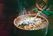 Steamed fish with vegetables in a bamboo steamer (Asia)