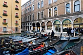 Gondolas moored in front of facade with arcades, Venice, Italy