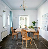 Dining room with stone flooring , table, chair and chandelier