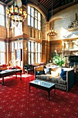 Fireplace room in hotel Bovey Castle with chandeliers, red carpet and sofas, Devon, UK