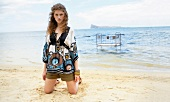Pretty woman with curly hair wearing patterned tunic kneeling on beach