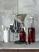 An arrangement of cherry-vanilla syrup in bottles and kitchen utensils