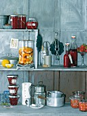 Various preserving jars and kitchen utensils on a shelf