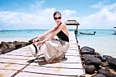Fashionable woman wearing sunglasses holding hat and crouching on jetty
