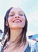 Frau, Kopf im Nacken, lächelt, Augen zu, Wasser läuft über ihr Gesicht