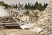 View of round stone houses with pointed roofs in Alberobello, Italy