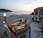 Tables laid on terrace besides illuminated torch at dusk