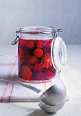 Grappa cherries with limes in a preserving jar