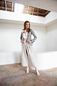 Frau in Blazer, Ansteckblume, breite Leinenhose, High-Heels, posiert
