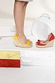 Gelbe und rote Keilabsatz-Sandalet- ten, gelbe, rote Taschen, Koffer