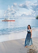 Pensive woman wearing jeans dress walking along beach and boats in background