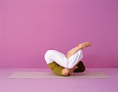 Pilates - Seal: Rückenlage, Beine zum Kopf, Hände an Füßen, Step 2