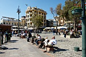 People sitting on benches in market place in Istanbul, Turkey