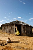Frau in  Abendgarderobe steht vor Eingang, Hütte, Afrika