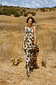 Beautiful brunette woman in evening dress walking with two lion cubs in steppe, Africa