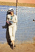 Young woman in beige hat and coat leaning against wall and looking at map of Marrakech