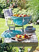 A portable barbecue on a wooden table in a summer garden