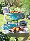 Tragbarer Kugelgrill auf Holztisch im sommerlichen Garten
