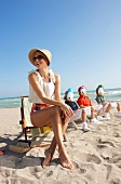 Woman wearing hat sitting on beach with three children wearing tick trick and track masks