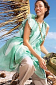 Cheerful brunette woman in green chiffon ruffle dress holding hat and smiling on beach