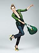 Frau, grüne Strickjacke, Shirt, Aus- schnitt, Pumps, steht auf 1 Bein