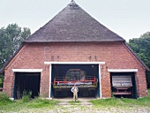 Man standing at the entrance of thatched farmhouse in Rieseby, Germany