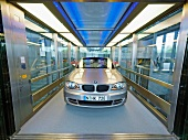 Silver convertible car in glass elevator, BMW World, Munich, Germany