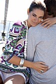 Portrait of beautiful woman wearing patterned tunic and necklace, hugging man and smiling