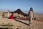 Woman wearing long oriental outfit walking while man building tent in desert