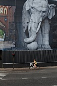 Girl riding bicycle beside building with elephant cladding in Copenhagen, Denmark