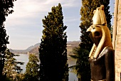 Golden figure, tree and lake in Morcote, Ticino, Switzerland