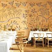 View of Hotel Haus Hirt restaurant with wooden table, chair and wall Ornaments, Austria