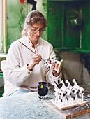 Artist Annette Kramer painting horse figurines