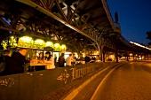 People dinning at restaurant under bridge in evening lights, Berlin, Germany