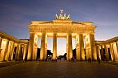 Berlin: Pariser Platz, Brandenburger Tor, beleuchtet, abends.
