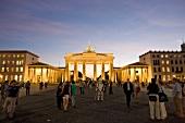 People at illuminated Brandenburg Gate and Pariser Platz at dusk, Berlin, Germany